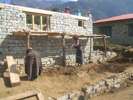 The Nepalese mud women mixing mud mortar