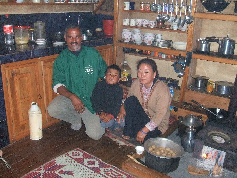 Purna the headmaster, his wife and son in their house