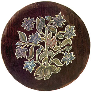 A stool cover showing a flower motif