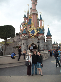 Mum and kids outside the castle in Disneyland