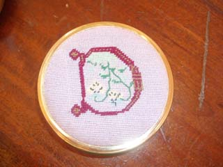 Decorated initial in needlepoint as a pin box made for Tracy in one of her earlier medieval roles