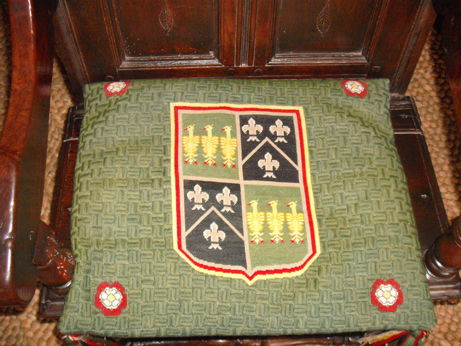 A needlepoint chair cushion with a combination of tent stitch for the heraldry and a basket weave stitch for the background